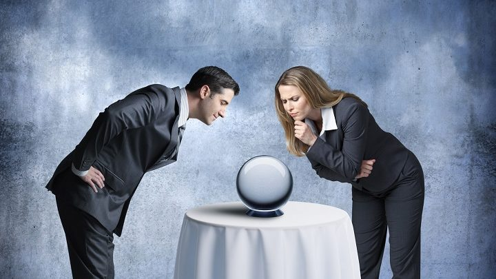 A businessman and a businesswoman look down at a crystal ball that sits on a tablecloth draped table in front of them.